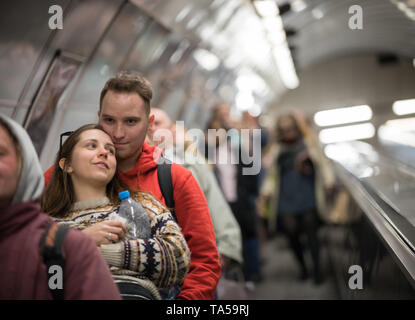 A young smiling couple going downstairs on escalator. Mid shot - Stock Image