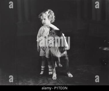 Shy little boy standing with his dog - Stock Image