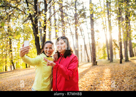 Two female runners with smartphone standing outdoors in forest in autumn nature, taking selfie when resting. - Stock Image