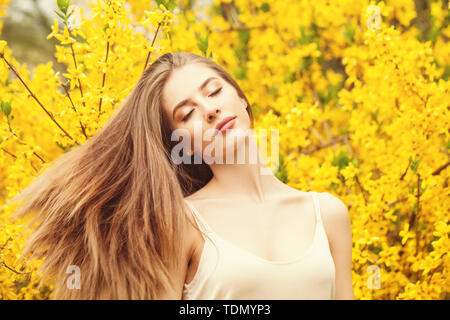 Cheerful woman with blowing hair outdoors - Stock Image