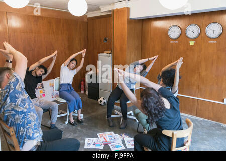 Creative business people stretching, taking a break in meeting - Stock Image