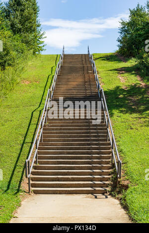 HICKORY, NC, USA-9/18/18: A concrete flight of steps with handrails lead up a grassy bank to the sky. - Stock Image