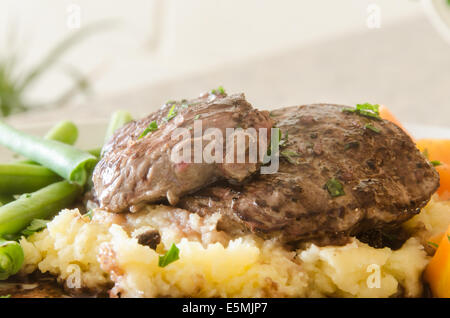 Pan fried venison loin on a bed of Irish mash with a juniper and red wine sauce - Stock Image
