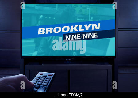 A man points a TV remote at the television which displays the Brooklyn Nine Nine main title screen (Editorial use only). - Stock Image