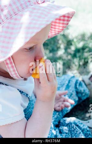 Girl eating plum - Stock Image