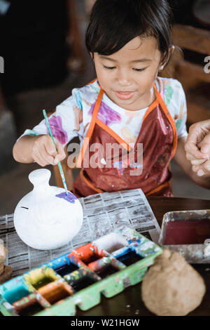 child painting ceramic pot with paint brush in pottery workshop - Stock Image