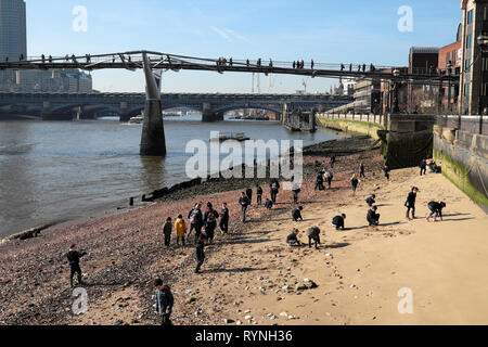 View of schoolchildren archaeology school group at low tide looking for artefacts on the foreshore of the River Thames London England UK  KATHY DEWITT - Stock Image