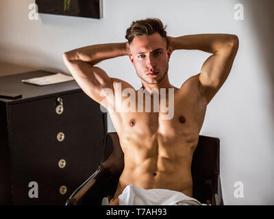 Shirtless naked sexy male model sitting on chair - Stock Image