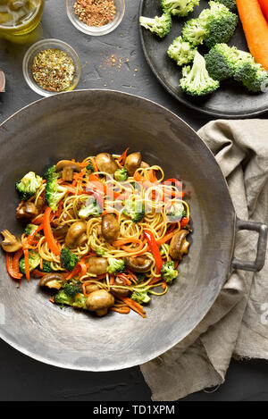 Tasty stir-fry noodles with vegetables in wok pan on black stone background. Top view, flat lay - Stock Image