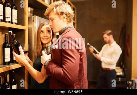 Young couple picks a bottle of red wine together at the shelf in the wine shop - Stock Image