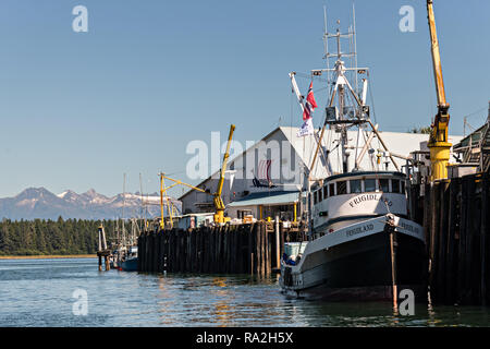 A fishing boat tied to the Icicle Seafoods dock in the tiny village of Petersburg on Mitkof Island along the Wrangell Narrows in Frederick Sound with the Alaska Coast Range of mountains behind on Mitkof Island, Alaska. Petersburg settled by Norwegian immigrant Peter Buschmann is known as Little Norway due to the high percentage of people of Scandinavian origin. - Stock Image