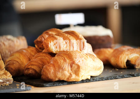 Freshly baked, golden, all butter, croissants for sale displayed on a slate counter top at a cafe delicatessen in - Stock Image