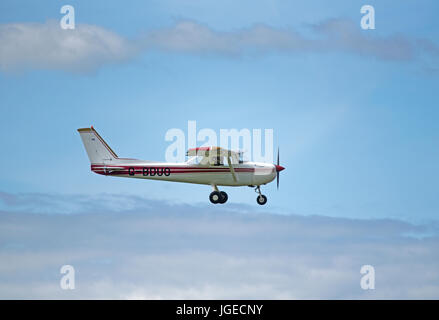 A Cessna 150m private light aircraft working out from Inverness Dalcross airport on a weekend flying sortie. - Stock Image