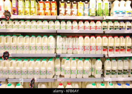 Fresh British milk on the shelves of a marks and spencer foodhall along with juice, fresh juices and smoothies - Stock Image
