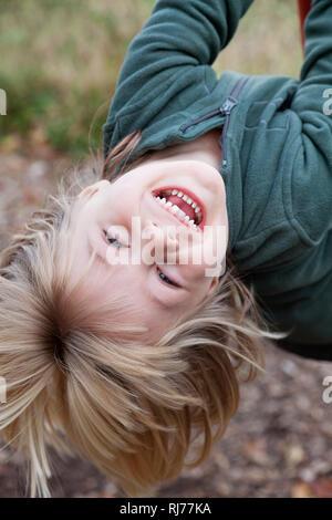 Vierjähriger Junge hängt kopfüber an einer Schaukel - Stock Image