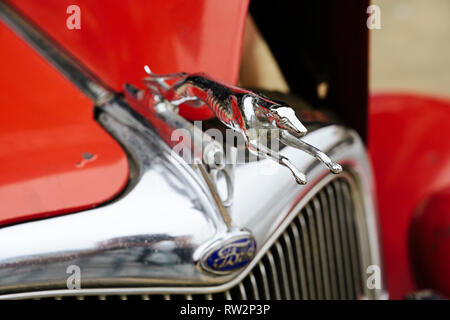 Vintage Ford Model 48 roadster greyhound hood ornament close up on the classic or antique two door car of the 1930s. - Stock Image