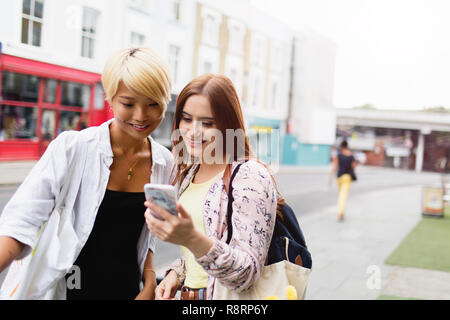 Young women friends texting with smart phone on urban street - Stock Image