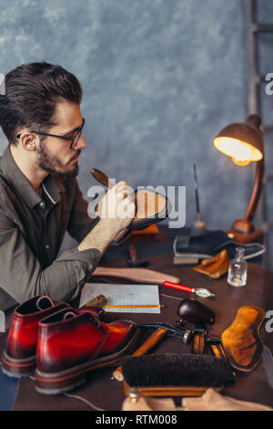 accurate working process in the shoe shop. close up side view photo. - Stock Image