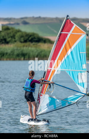 Young girl learning to windsurf on a lake - Stock Image