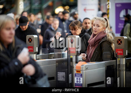 Manchester Victoria railway station busy scene as run hour passengers pass through the automated ticket barriers - Stock Image