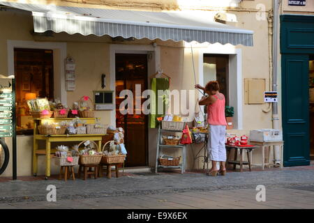 Woman closing her souvenir shop at end of the day in south of France - Stock Image