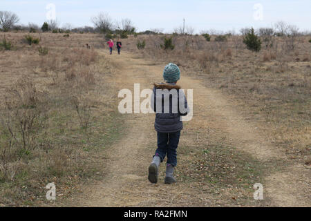 Girls hiking in the countryside with dog on cold winter day - Stock Image