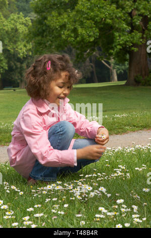 Little girl picking daisies in the local park - Stock Image