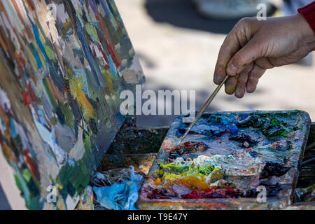 Closeup of unrecognizable man holding artists palette and mixing colors while painting - Stock Image
