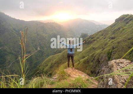 Woman standing with raised hands on the top of Small Adams peak. Ella, Sri Lanka - Stock Image
