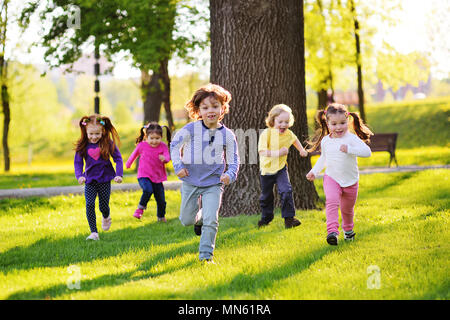 many young children smiling running along the grass in the park. - Stock Image
