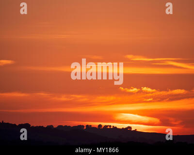 Ashbourne, Derbyshire. 5th Jun, 2018. UK Weather: spectacular sunset over the ancient woods Hazleton Clump Cairn near Thorpe taken from Ashbourne Derbyshire, Peak District National Park Credit: Doug Blane/Alamy Live News - Stock Image