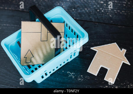 buying decor items or furniture concept: shopping basket with parcel and small cardboard house next to it - Stock Image