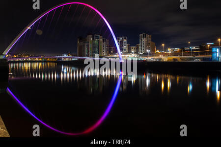 Gateshead, England, UK - February 3, 2019: The Baltic Flour Mills and modern apartment buildings are reflected in the River Tyne at night along Gatesh - Stock Image