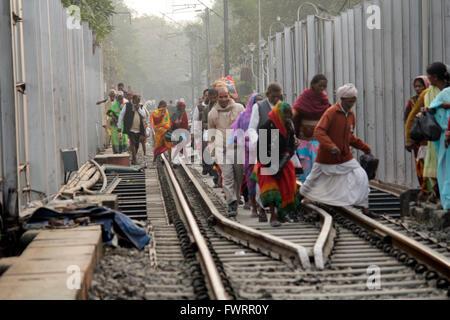 People walking on railway tracks in a crowded Kolkata, India - Stock Image