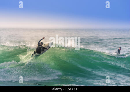 A surfer carving a wave at popular surfing hotspot Fistral beach in Newquay in Cornwall. - Stock Image
