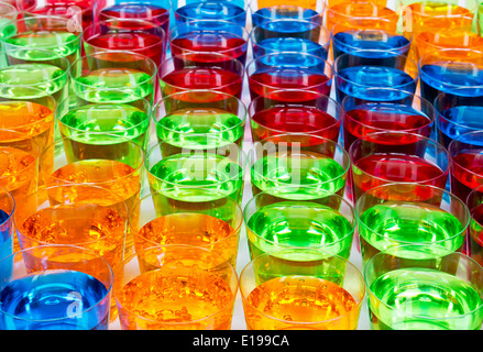 Various alcoholic shots in shot glasses creating multi colored drinks industry background - Stock Image