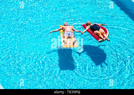 Old people senior couple relax and sleep on the blue swimming pool clear water lay down on trendy coloured inflatabler mattress lilos and taking hands - Stock Image