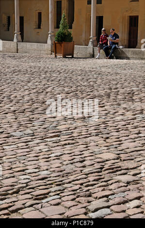 Seated couple reading brochure in front of stone sets paving in courtyard of Hotel Dieu medieval hospital Beane France - Stock Image
