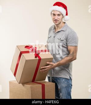 Handsome man in santa hat - hand gift box - Stock Image