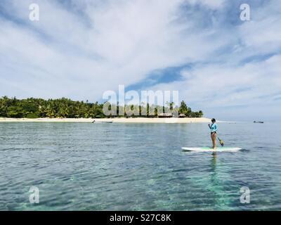 A female stand up paddling. Tavarua island, Fiji. - Stock Image