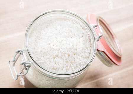 High Angle View Of An Open Jar Of Rice On Wooden Table - Stock Image