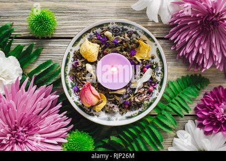 Decorative Plate with Purple Candle, Dried Herbs, Dried Flowers and Spring Flowers - Stock Image