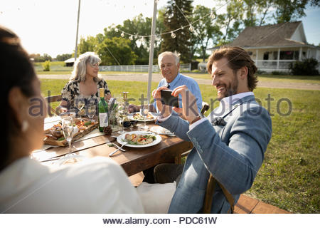 Man with camera phone photographing friends at sunny, rural garden party lunch - Stock Image