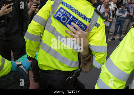 A protester is arrested by Met police officers at Oxford Circus on day 4 of protests by climate change environmental activists with pressure group Extinction Rebellion, on18th April 2019, in London, England. - Stock Image
