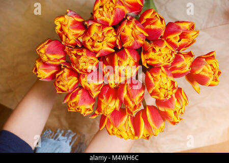 Fresh, red and yellow bouquet of flowers in a woman's hand on craft paper, spring, the eighth of March. Bicolours - Stock Image