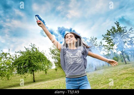 Happy laughing young girl trailing a smoke flare in a cloud of colorful blue smoke as she runs towards the camera holding it aloft in a spring park - Stock Image