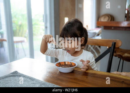 asian beautiful toddler girl having breakfast by herself in the morning at dining room - Stock Image