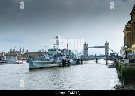 The tourist attraction HMS Belfast moored on the River Thames in London with the Tower of London and Tower Bridge in the background. - Stock Image