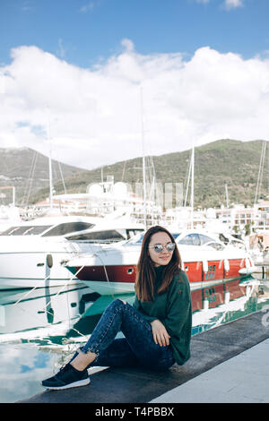 A beautiful young girl in sunglasses is sitting next to yachts in Porto Montenegro in Tivat in Montenegro. - Stock Image