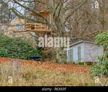 Garden tree house with swing underneath - Stock Image